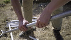 Closeup Of Man Connecting Large Tent Poles Together Stock Footage