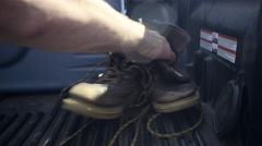 Closeup Of Man's Hands Grabbing A Pair Of Old Boots From Truck Bed Stock Footage