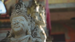 Balinese men stone statues, slide and tilt up Stock Footage
