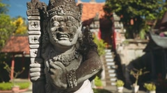 Balinese man stone statue in front of balinese gates and fountain, slide Stock Footage