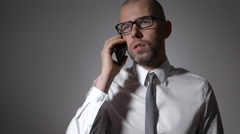 Businessman leads a serious conversation with a colleague on the phone Stock Footage