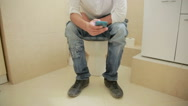 Man sitting on a toilet and looks in the cell phone Stock Footage