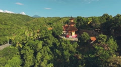 Aerial view of orange temple tower on green hill, Brahma Vihara Arama Monastery Stock Footage