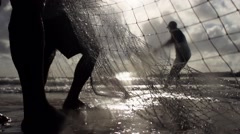 Fisherman pulling net at sea in slowmotion Stock Footage