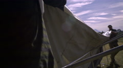 Two Men Setup Their Large Hunting Tent In Field Stock Footage