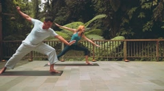 Bali yoga teacher and caucasian woman in warrior and extended side angle pose Stock Footage