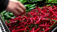 Woman's hand picking red chili peppers  inside Save on foods store Stock Footage