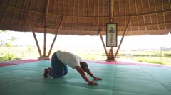 Sun salutation part with eight limb pose, by balinese man doing yoga Stock Footage