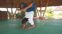 Scorpion pose, vrischikasana by balinese man doing yoga in a gazebo Stock Footage