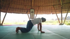 Sun salutation part with Downward-Facing Dog pose by balinese man doing yoga Stock Footage
