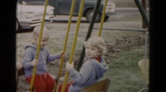1962: blonde twin siblings playing on seesaw teeter totter playground swing Stock Footage