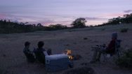 Hunters Sit Around A Campfire At Sunset, They Talk, One Whittles A Piece Of Wood Stock Footage