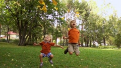 Happy boys throws yellow leaves in autumn Stock Footage