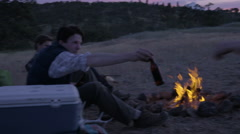 Hunters Sit Around Campfire, Man Passes His Brother A Beer Stock Footage