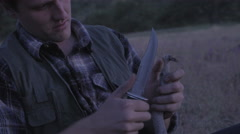 Hunter Whittles A Piece Of Wood, Passes His Hunting Knife To His Friend Stock Footage