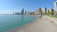 Slim Ethnic African American male running along Chicago shoreline by skyscrapers Stock Footage