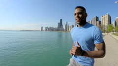 Healthy Ethnic African American male running along Chicago city shoreline Stock Footage