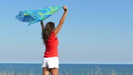 Slow motion. Slender Woman in red with cape  against  sea.  Stock Footage