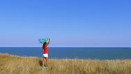 Slow motion. Sexy woman in red with cape  against  sea. Focus change Stock Footage
