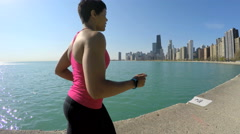 Profile of Ethnic African American female running in Chicago city by shoreline Stock Footage