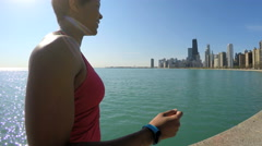 Fit Ethnic African American female running in sportswear by Chicago shoreline Stock Footage