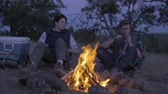 Man Whittles Piece Of Wood By Campfire, Friend Asks To See His Knife, Lets Him Stock Footage