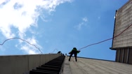 Fearless people descend down with safety cord on skyscraper high building wall Stock Footage