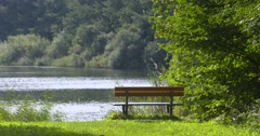 Empty park bench at lakeside - no people Stock Footage