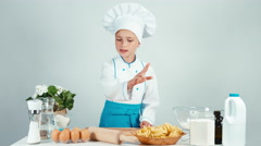 Portrait young baker girl holds rolling pin in the kitchen smiling at camera Stock Footage