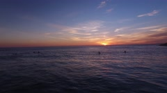 Surfers in the water during a beautiful sunset aerial view Stock Footage