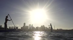 Couple in stand up paddle at Natal sunset in slowmotion Stock Footage