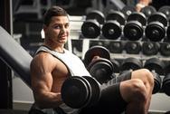 Pleasant athletic man lifting dumbbells Stock Photos