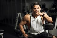 Handsome well built weightlifter sitting thoughtfully Stock Photos