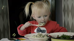 Dolly Girl Eating Porridge at home Alone at a table in the Kitchen Stock Footage