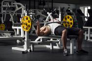 Strong athletic man preparing to lift a barbell Stock Photos