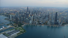 Aerial illuminated sunset view of Lake Michigan Navy Pier Hancock Center Chicago Stock Footage