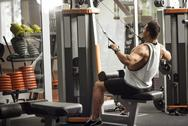 Strong professional sportsman training on a gym apparatus Stock Photos