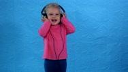 Woman put big headphones on girl head and child enjoy music Stock Footage