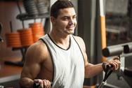 Happy confident man training in a gym hall Stock Photos