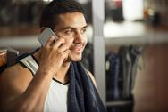 Happy handsome sportsman talking on the phone Stock Photos