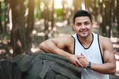 Happy well built man leaning on the tire Stock Photos