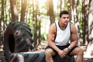Handsome thoughtful man sitting on the tire Stock Photos