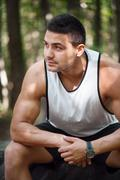 Serious well built man sitting in the park Stock Photos