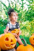 Halloween. Child dressed in black with jack-o-lantern in hand, trick or treat Stock Photos