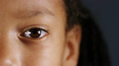 Close up of one eye of a young child looking straight to camera Stock Footage