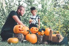 Daughter near father who pulls seeds and fibrous material from a pumpkin befo Stock Photos