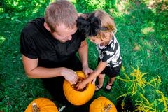 Daughter and father pulls seeds and fibrous material from a pumpkin before ca Stock Photos