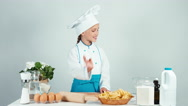 Baker girl holds rolling pin in the kitchen smiling at camera isolated on white Stock Footage