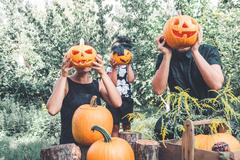 Family holding halloween pumpkin in front of their faces, preparation for par Stock Photos