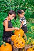 Daughter and mother pulls seeds and fibrous material from a pumpkin before ca Stock Photos